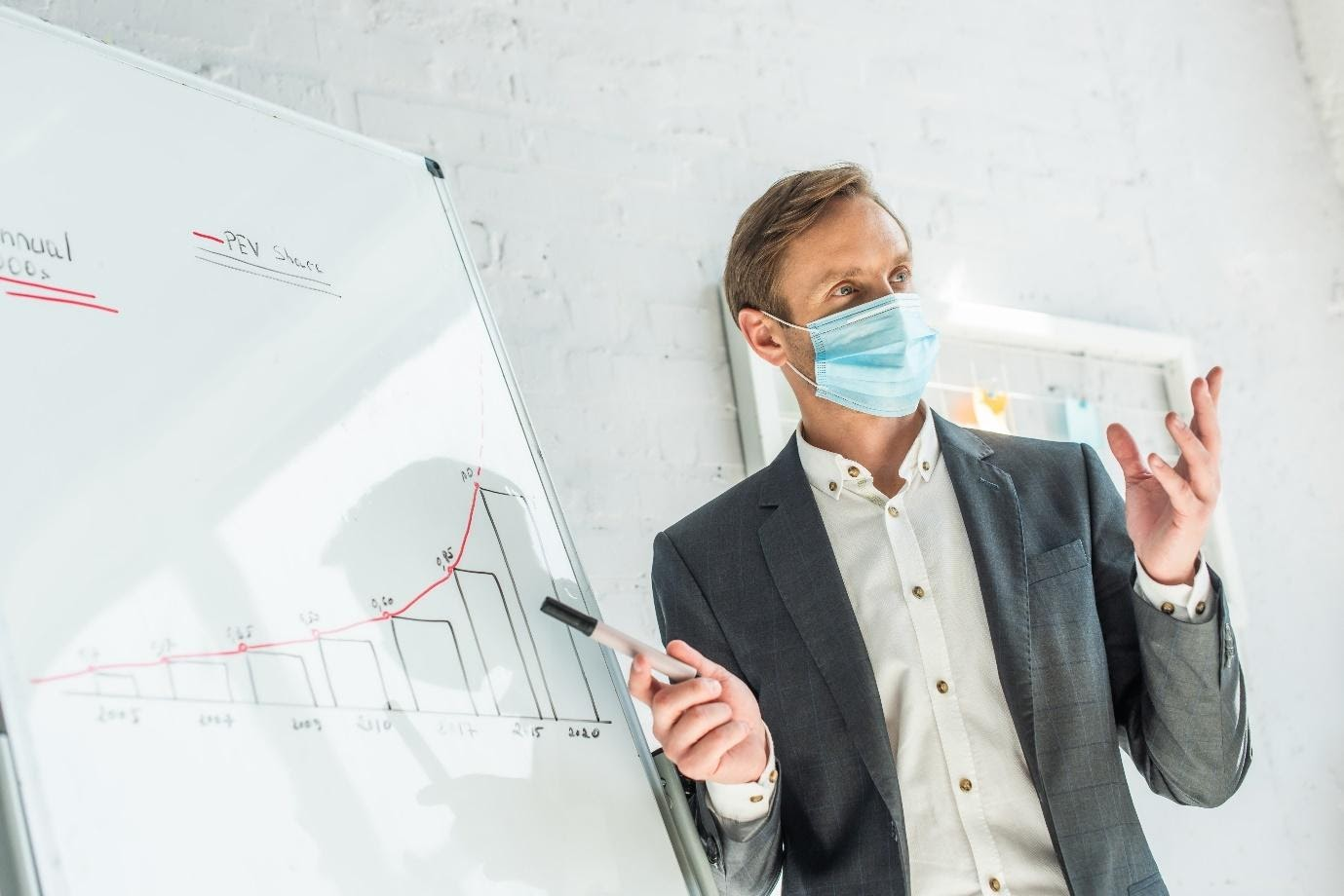 A person wearing a mask and holding a pen  Description automatically generated with low confidence
